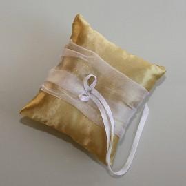 Vankušik so zlatého saténu so širokou trblietavou stuhou a kamienkom v tvare srdiečka.